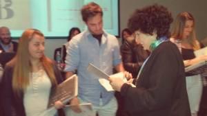 """Luisa entrega una letra de su """"ABC de las microfábulas"""" a cada uno de los alumnos que participaron del proyecto."""